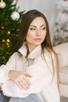 긴 머리와 크리스마스 트리 근처 누드 메이크업 세련된 여자의 초상화. 아늑한 휴가