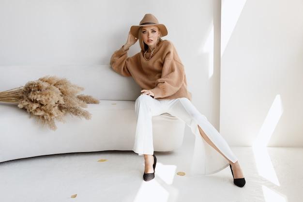 明るいスタジオで秋の服を着たスタイリッシュなモデルの肖像画。テキスト用の空き容量