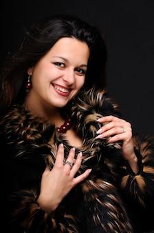 黒い背景の上のスタジオでポーズをとってスタイリッシュな笑顔のポジティブな若い女性の肖像画
