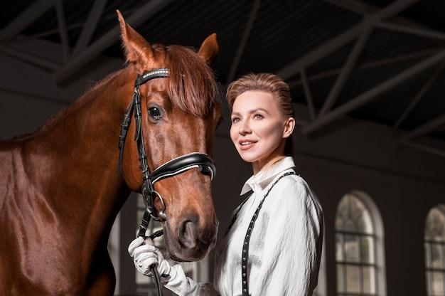 Портрет стильной женщины, обнимающей породистую лошадь. концепция любви и заботы. смешанная техника