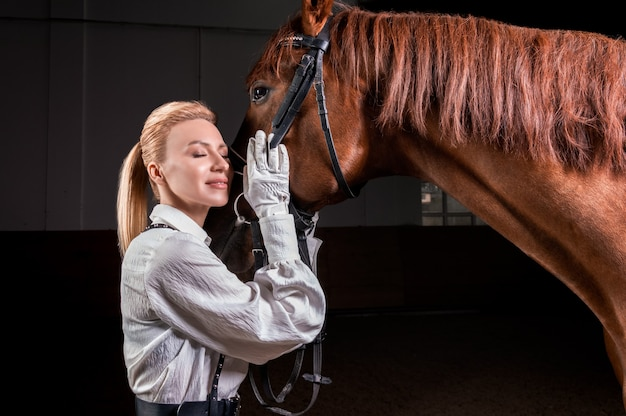 Портрет стильной женщины, обнимающей породистую лошадь. концепция любви и заботы. Premium Фотографии