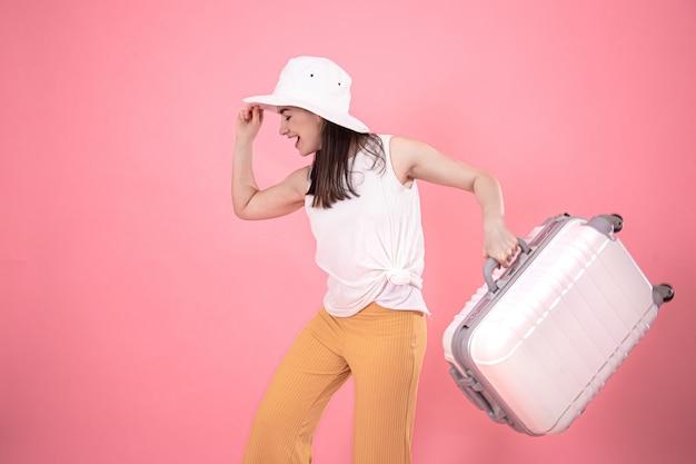 Портрет стильной женщины в модной летней одежде и белой шляпе на розовом с чемоданом для путешествий.