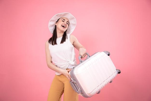 여행 가방으로 분홍색 배경에 세련 된 여자의 초상화.