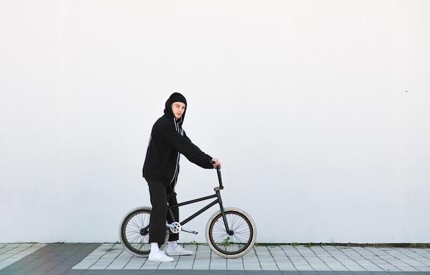 Портрет стильного молодого человека с велосипедом bmx на белой стене.