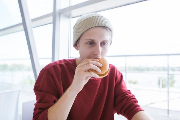 Портрет стильного молодого человека с гамбургером в руках на светлом фоне