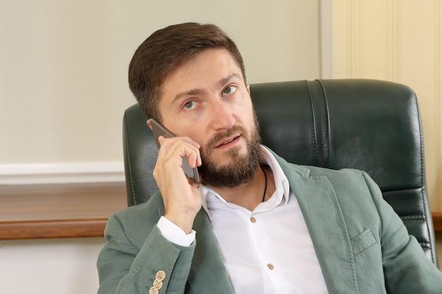 Портрет успешного делового человека с мобильным телефоном в офисе