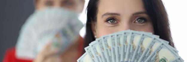 그녀의 얼굴 앞에서 손에 미국 달러를 들고 성공적인 사업가의 초상화. 팀워크 이익 개념.
