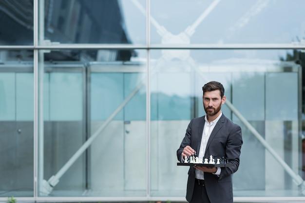 チェスを手にボードを持って成功した真面目なビジネスマンの肖像画は、一歩を踏み出すことを提案します