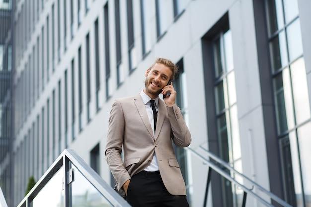 성공적인 젊은 사업가의 초상화입니다. 현대적인 비즈니스 센터를 배경으로 전화기가 있는 흰 셔츠를 입은 곱슬머리 남자.