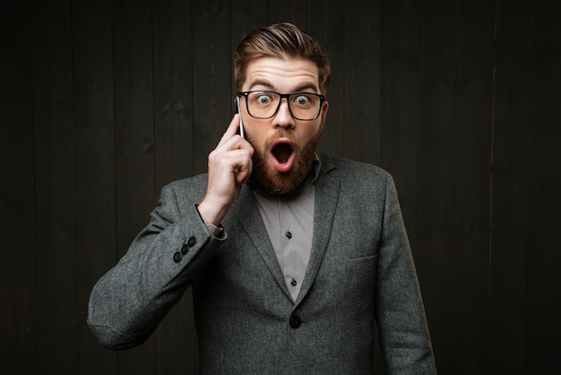검은 나무 배경에 격리된 휴대폰으로 통화하는 안경을 쓴 놀란 놀란 남자의 초상화
