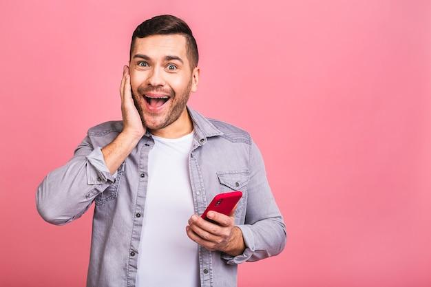 Портрет удивленного пораженного потрясенного случайного молодого человека, смотрящего на мобильный телефон. используя телефон, отправляя текстовое сообщение.