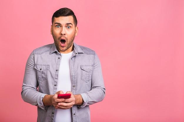 Портрет удивленного, пораженного шокированного случайного молодого человека, смотрящего на мобильный телефон
