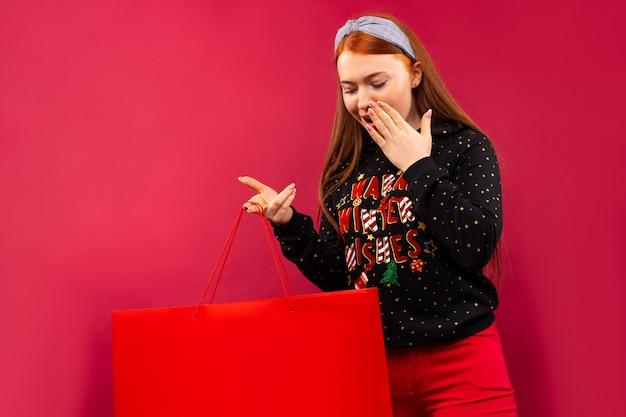 開いたギフトバッグを見て驚いて幸せな女性の肖像画