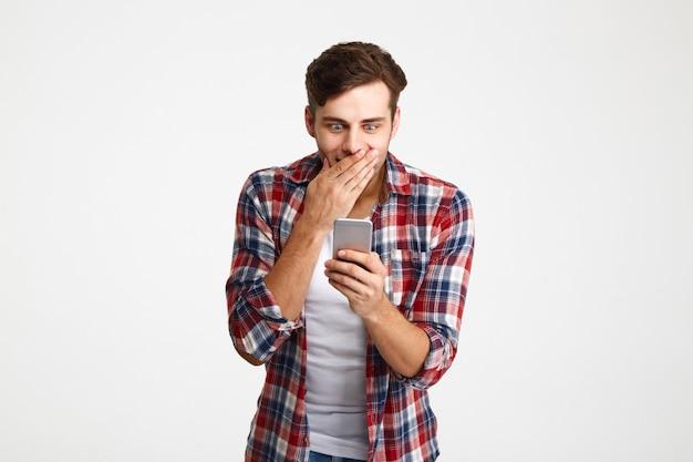 Портрет удивленного случайного человека, смотрящего на мобильный телефон
