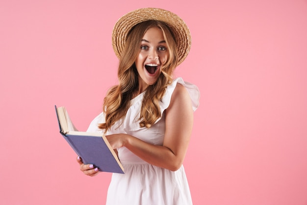 Портрет удивленной милой молодой красивой женщины, позирующей изолированной над розовой настенной книгой для чтения с открытым ртом.