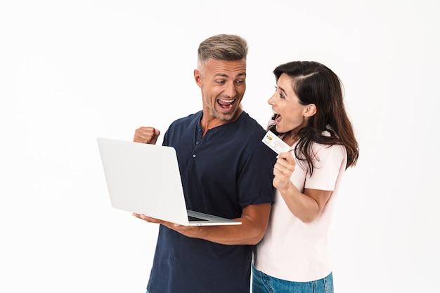 Портрет удивленной эмоциональной взрослой влюбленной пары, изолированной над белой стеной с помощью портативного компьютера, делает жест победителя, держащего кредитную карту.