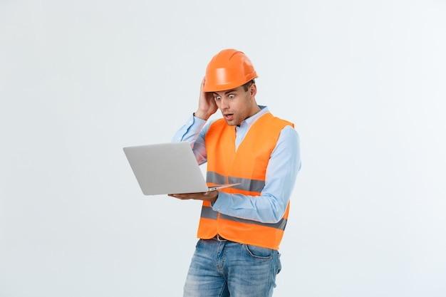 회색 배경 위에 노트북을 들고 놀란 엔지니어의 초상화.