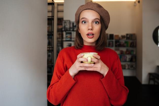 Портрет удивленной девушки, одетой в свитер