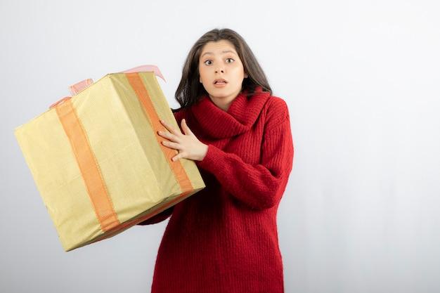흰 벽 위에 격리된 선물 상자를 들고 놀란 소녀의 초상화.