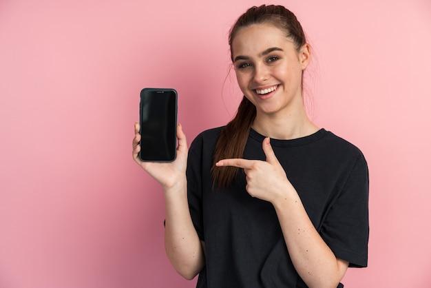 Портрет удивленной девушки, указывающей пальцем на пустой экран мобильного телефона