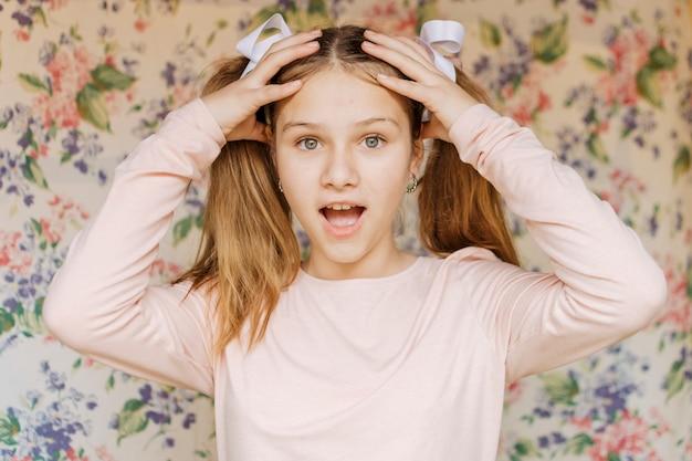 頭に手を持つ驚くべき女の子の肖像