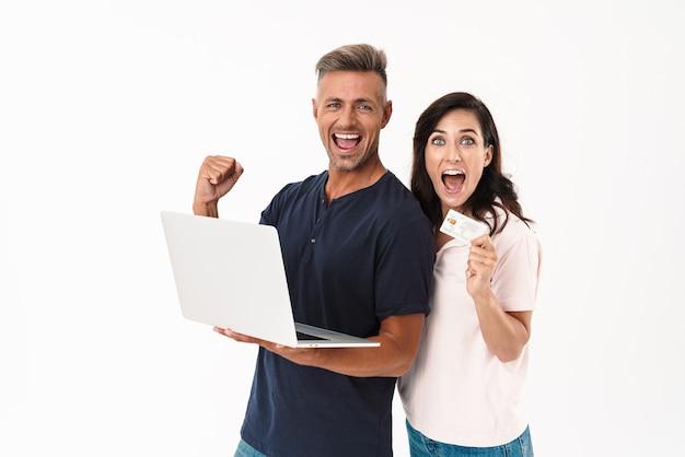 Портрет удивленной шокированной взрослой влюбленной пары, изолированной над белой стеной с помощью портативного компьютера, делает жест победителя, держащего кредитную карту.
