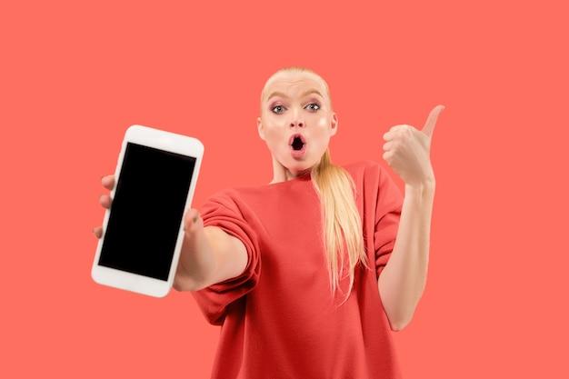 Портрет удивленной, улыбающейся, счастливой, удивленной девушки, показывающей пустой экран мобильного телефона, изолированного на коралловом фоне.