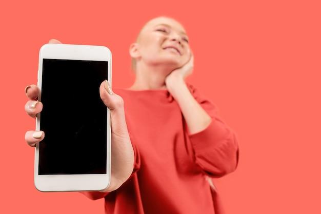 Портрет удивленной, улыбающейся, счастливой, удивленной девушки показывая пустой экран мобильного телефона, изолированного на коралловом фоне.
