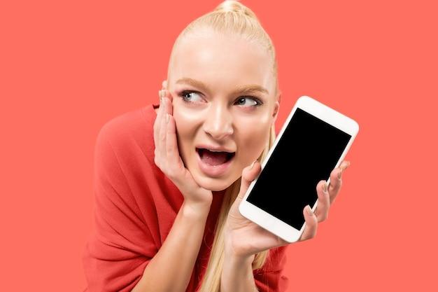 珊瑚の背景の上に分離された空白の画面の携帯電話を示している驚き、笑顔、幸せ、驚きの少女の肖像画。