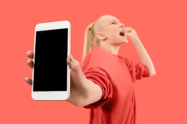 珊瑚の背景の上に分離された空白の画面の携帯電話を示す驚き、笑顔、幸せ、驚きの少女の肖像画。