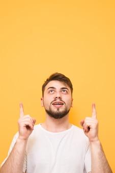 Портрет удивленного подростка в белой футболке, стоящего на желтом, смотрящего вверх и показывающего пальцами на пустом месте