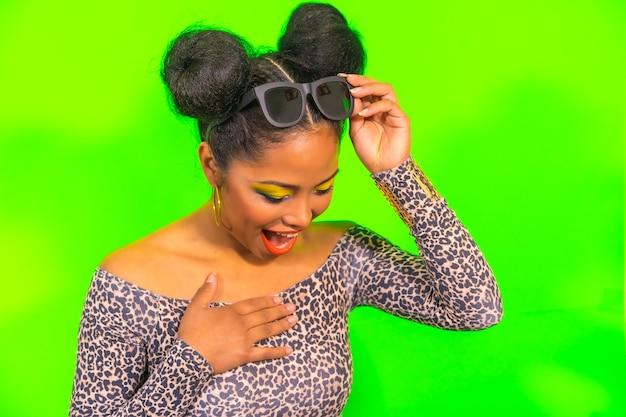 Портрет удивленной женщины с ярким макияжем и прической с двумя боковыми пучками в стильных солнцезащитных очках