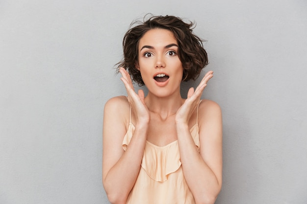 Портрет удивленной женщины с руками на ее лице