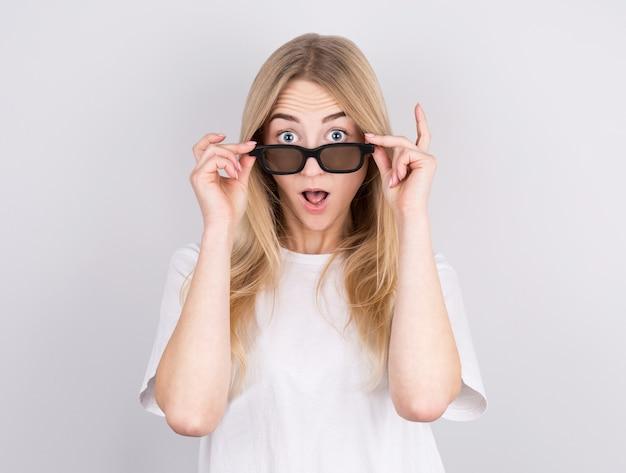 Портрет удивленной молодой красивой девушки в очках, глядя на камеру, пока поднял очки.
