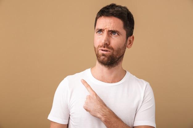 Портрет удивленного молодого человека, небрежно одетого, стоящего изолированно на бежевом фоне и указывая на копировальное пространство