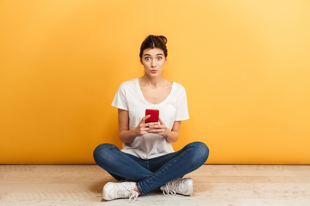 携帯電話を保持している驚きの若い女性の肖像画