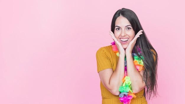Портрет удивлен молодой женщины на розовом фоне