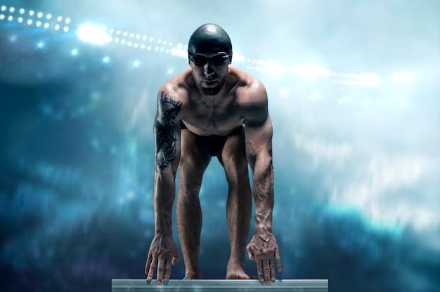 Портрет пловца на фоне спортивной арены. спортсмен готовится к прыжку