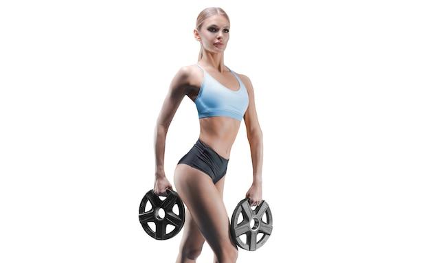 Портрет высокой спортивной женщины с весовыми плитами в руках на белой стене.