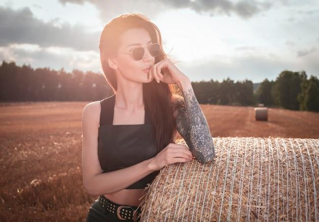 석양에 건초 더미의 배경에 선글라스에 문신을 한 소녀의 초상화. 혼합 매체