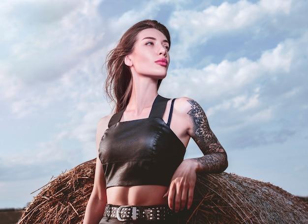 해질녘 건초더미의 배경에 문신을 한 소녀의 초상화. 혼합 매체
