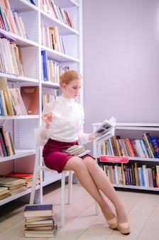 Портрет учителя, читающего книгу в библиотеке