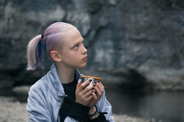 Портрет девушки-подростка, отдыхающей с кружкой на берегу реки, глядя на прибрежные скалы