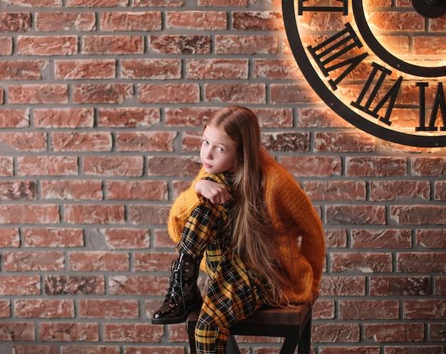 飾られた壁の背景に10代の少女の肖像画