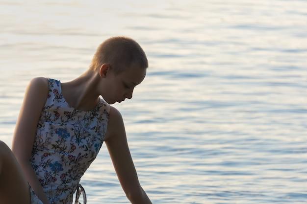 水面の背景にドレスを着た短い散髪の10代の少女の肖像画