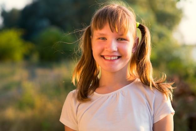 Портрет девушки-подростка на природе на фоне травы и деревьев