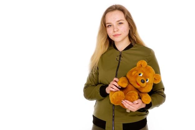 Портрет девочки-подростка с плюшевым мишкой в руках на белом