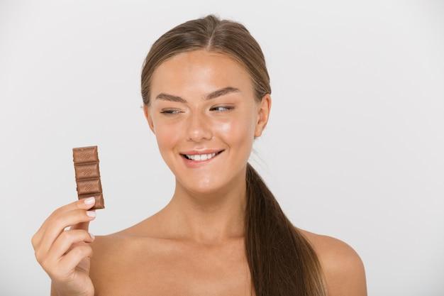 孤立したチョコレートの断片を保持している魅力的な若いトップレスの女性の肖像画