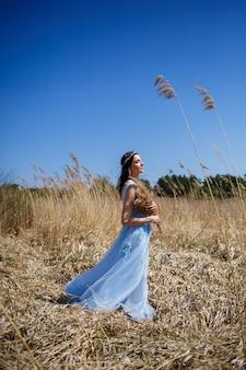 Портрет нежной девушки в голубом длинном платье в сухом горошине с улыбкой на лице в солнечный теплый летний день