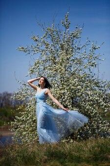 화창한 여름날 그녀의 얼굴에 미소를 띠고 꽃이 만발한 나무 아래 파란색 긴 드레스를 입은 부드러운 소녀의 초상화